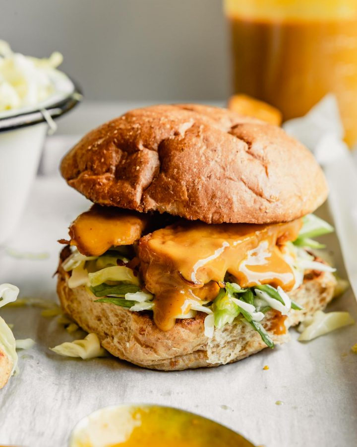 vegan bbq tempeh sandwich set on parchment paper with additional bbq sauce in a jar behind it