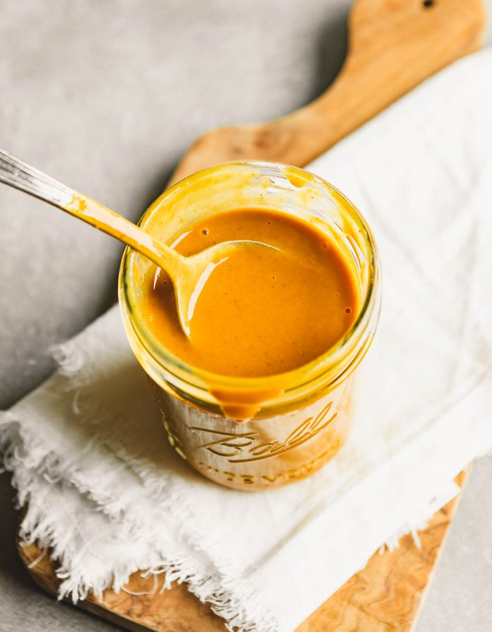 yellow-orange sauce being spooned fro a glass jar
