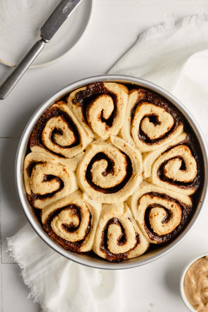overhead image of baked cinnamon rolls in a round cake pan