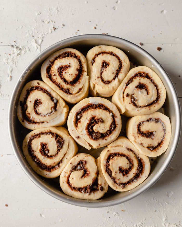 overhead image of unbaked, proofed cinnamon rolls in a round cake pan