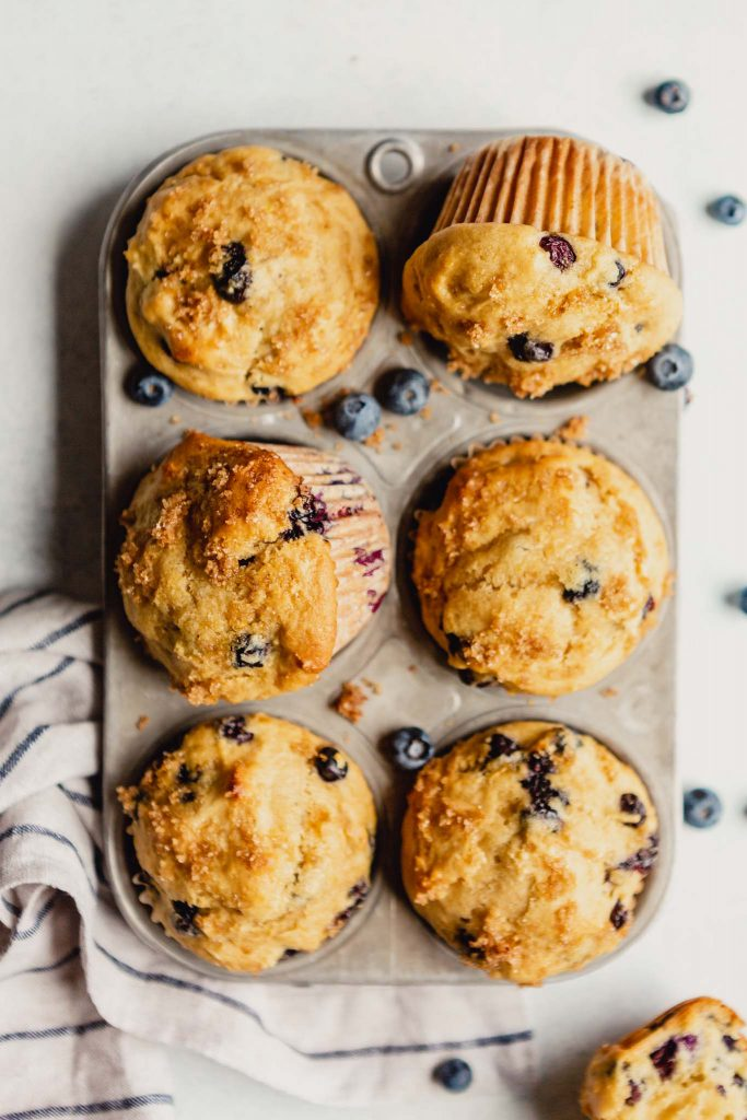muffins in a muffin tin with blueberries scattered around it