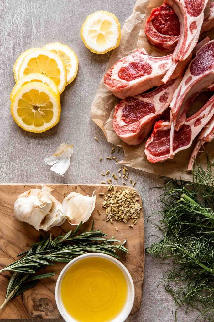 overhead image of raw lamb rib chops, lemon slices, garlic, fennel seeds, fresh rosemary and olive oil arranged on a counter top