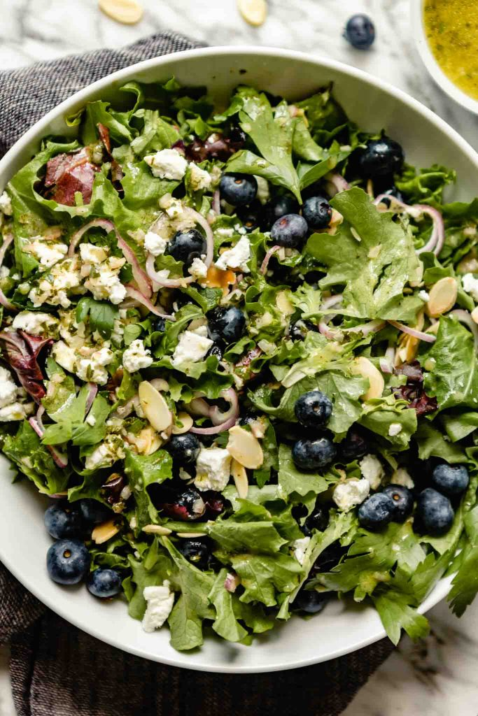 image of a large white bowl filled with salad greens, blueberries, shallot, almonds, and goat cheese
