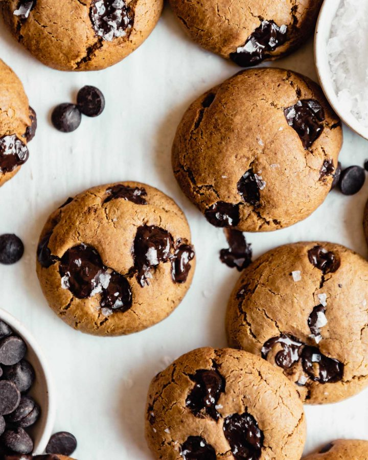 chocolate chip cookies arranged on parchment paper with a bowl of chocolate chips to the bottom left and salt to the top right
