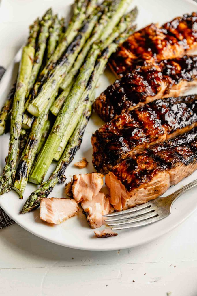 glazed salmon fillets on a plate with grilled asparagus