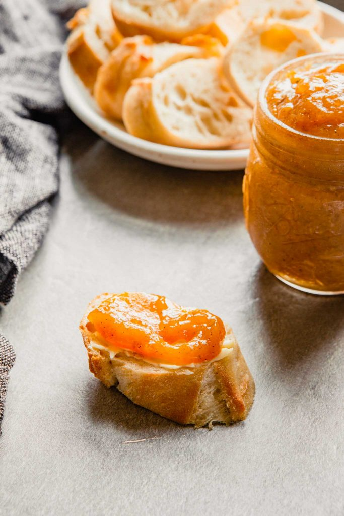 peach jam spread on a slice of baguette with butter
