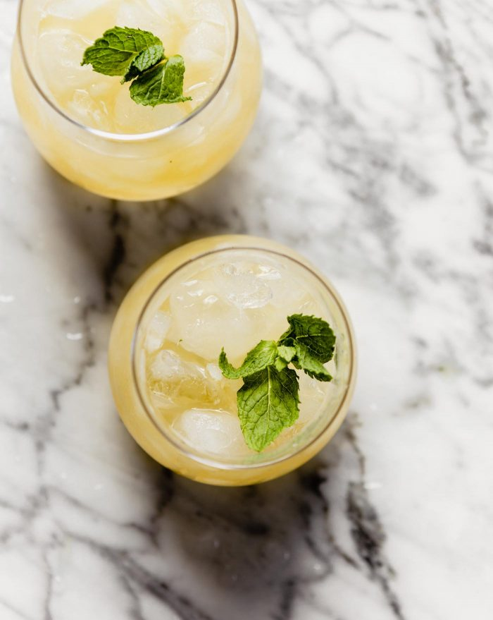 overhead image of two bourbon smash cocktails on a marble countertop