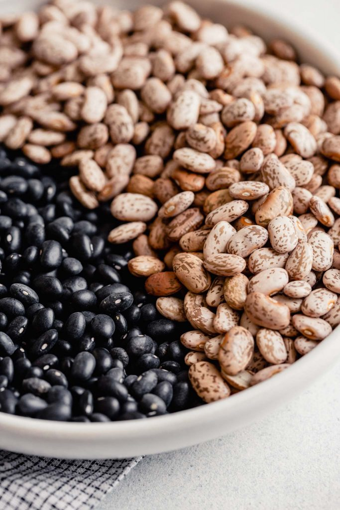 dry black beans and pinto beans in a white bowl