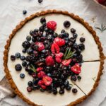 tart set on parchment paper with berries scattered around