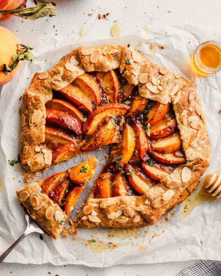 peach galette set on a piece or parchment paper with a slice being taken out