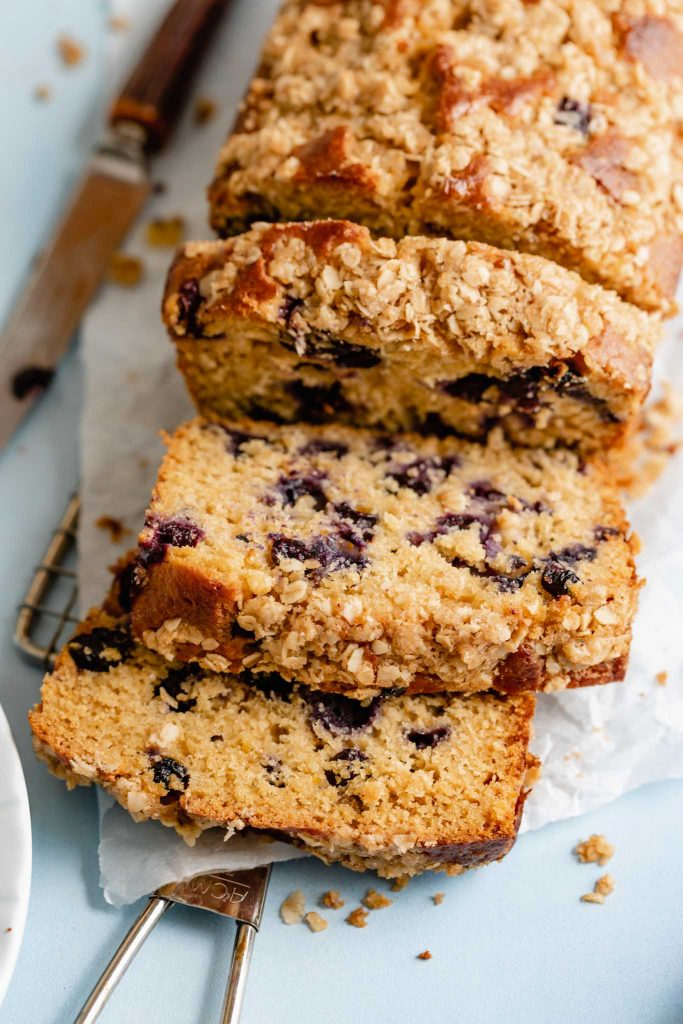 slices of lemon blueberry bread laying on each other on a piece of parchment paper