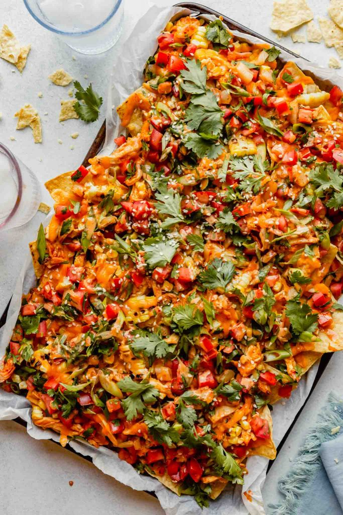 nachos on a baking sheet topped with cilantro, tomatoes, kimchi, melted cheddar cheese and a sauce