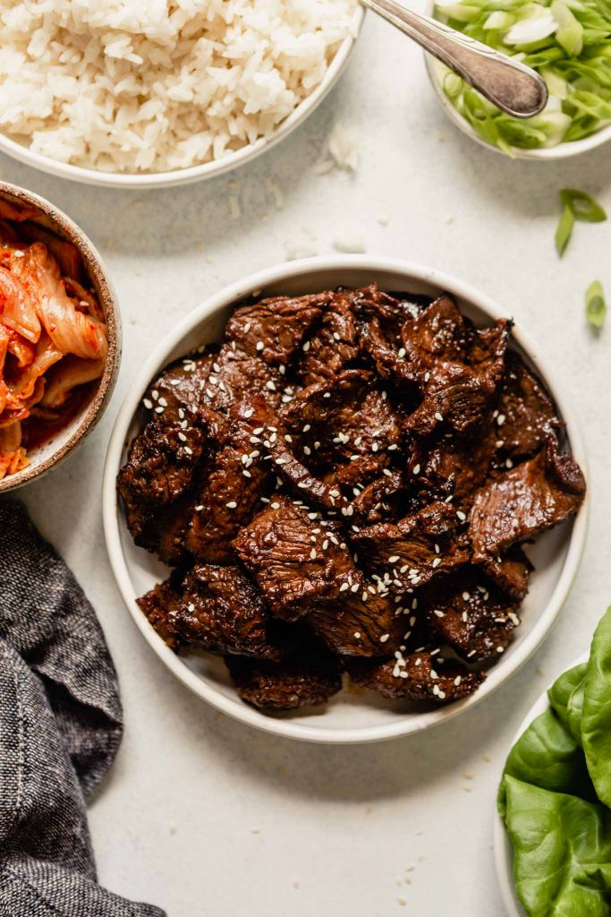 grilled beef in a white bowl set on a table with kimchi, rice, and scallions set around it