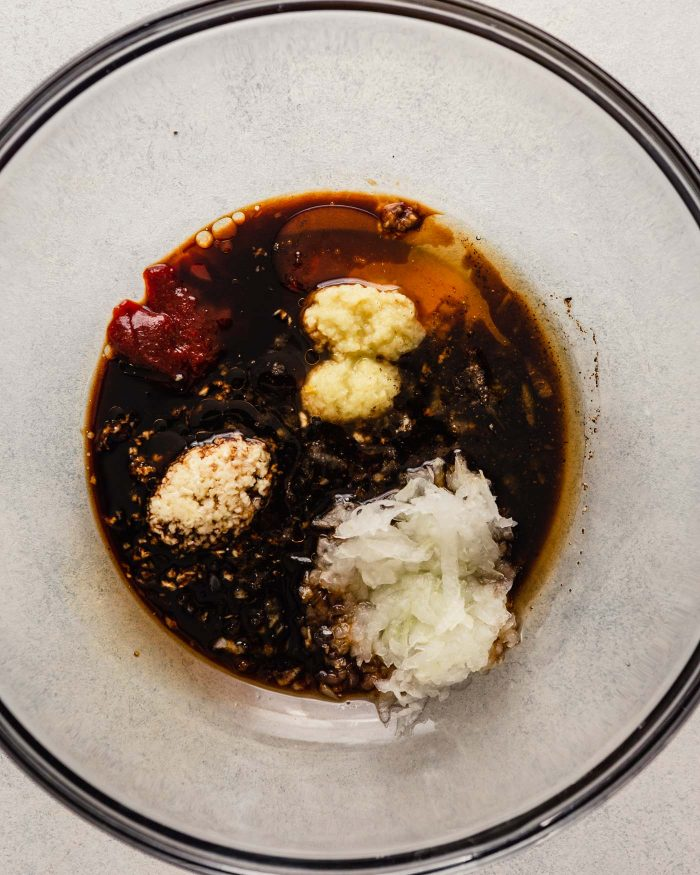 glass bowl filled with ingredients for a bulgogi marinade–soy sauce, grated onion, ginger, honey, mirin, gochujang, sesame oil, gallic cloves
