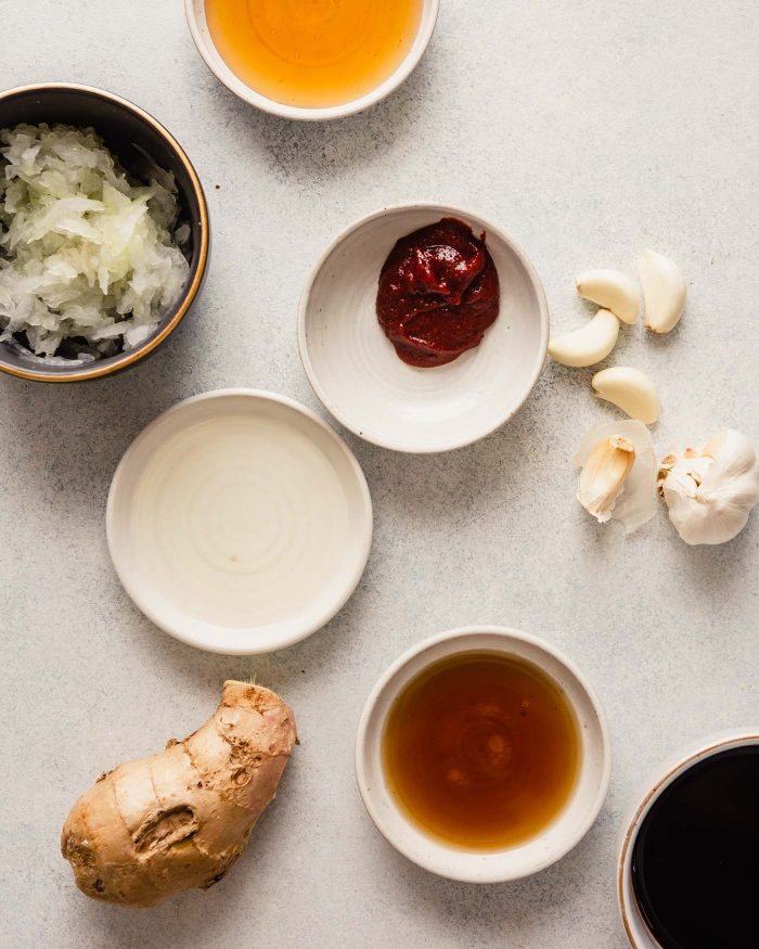 small white bowls filled with ingredients for the bulgogi marinade—soy sauce, grated onion, ginger, honey, mirin, gochujang, sesame oil, gallic cloves