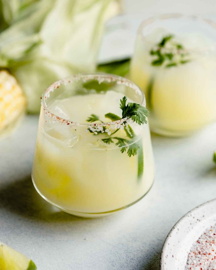 cocktail glass filled with a creamy yellow cocktail and garnished with cilantro.