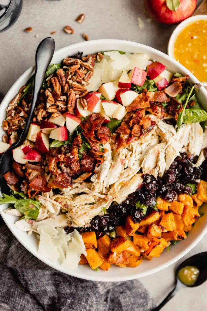 large white bowl filled with dark lettuce greens topped with pecans, apples, Manchego cheese, bacon, chicken, cranberries and squash