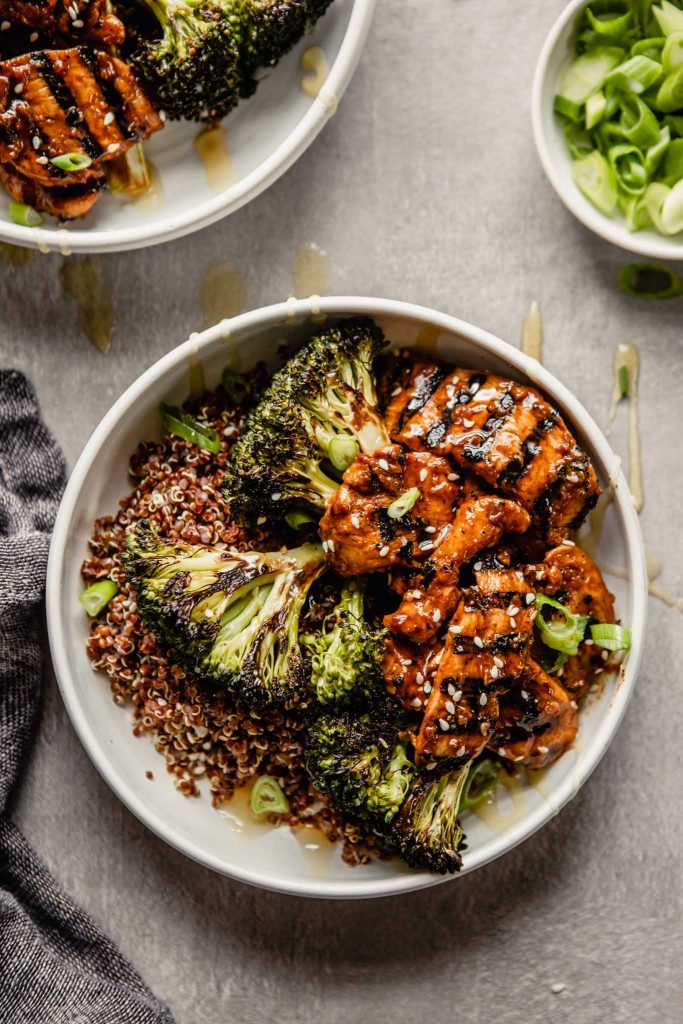 white bowls filled with quinoa and topped with roasted broccoli and charred meat