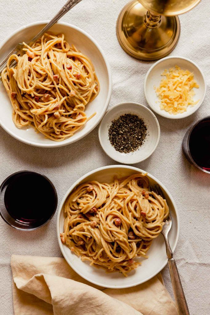 carbonara in two white bowls set on a table with glasses of red wine, shredded gouda, and black pepper