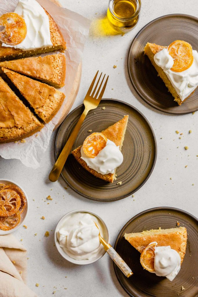 Slices of cake on brown plates topped with whipped cream and candied citrus