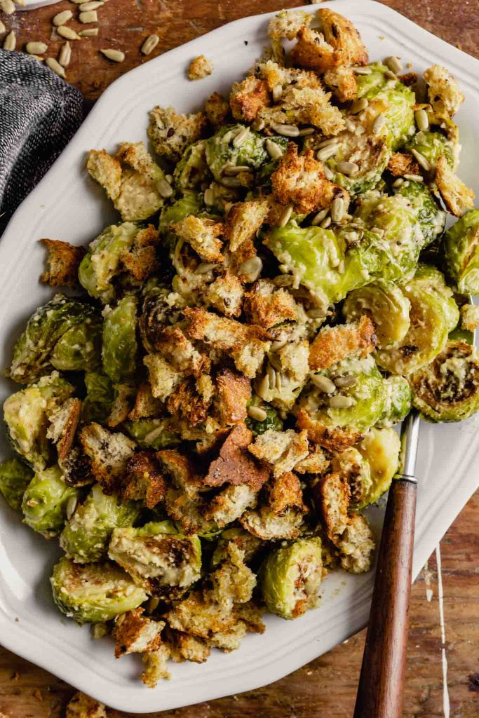 roasted brussels sprout salad on a white oval plate set on a messy wooden table