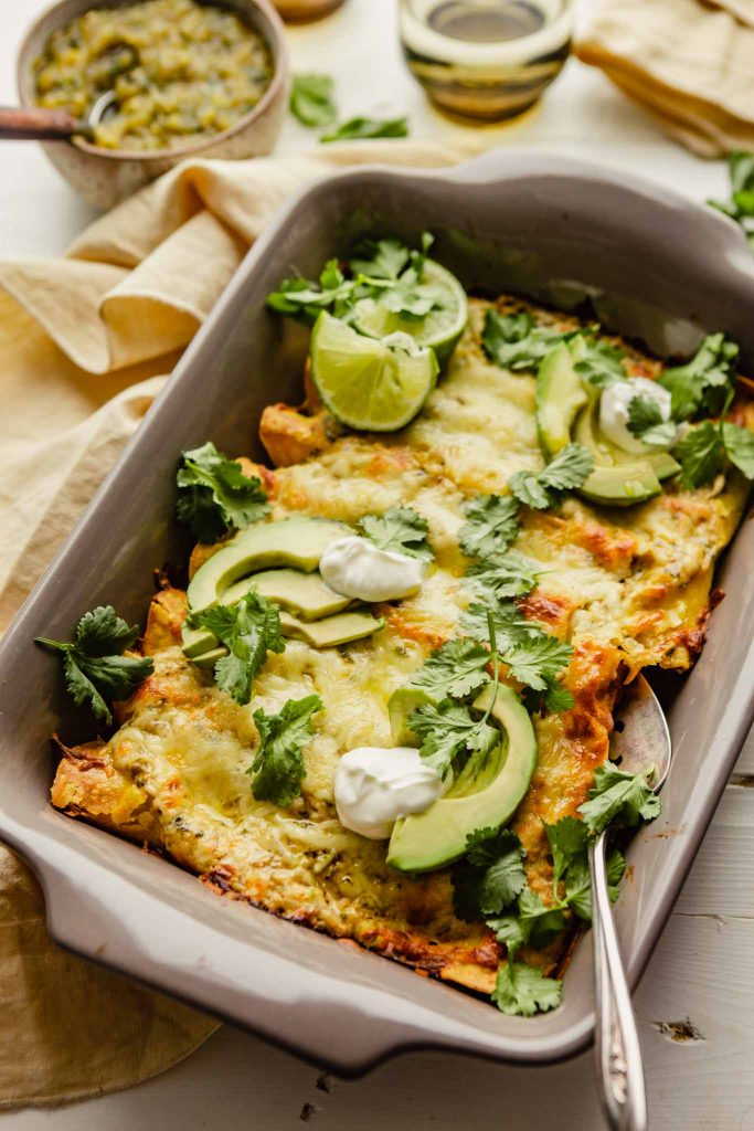 enchiladas verde in a gray pan set on a white table with salsa and yellow napkins set around.