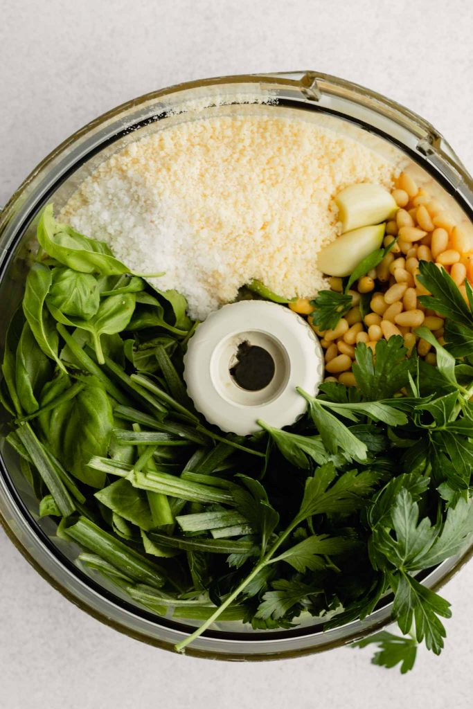 Food processor bowl filled with basil, chives, garlic cloves, parsley, pine nuts, parmesan cheese, and salt