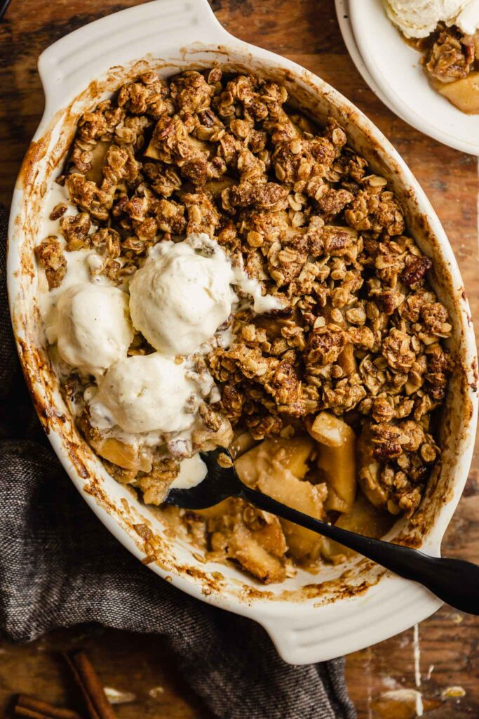 apple crisp in a white oval baking dish set on a wood table. three scoops of ice cream set on top of the crisp with and a black spoon set in the crisp.