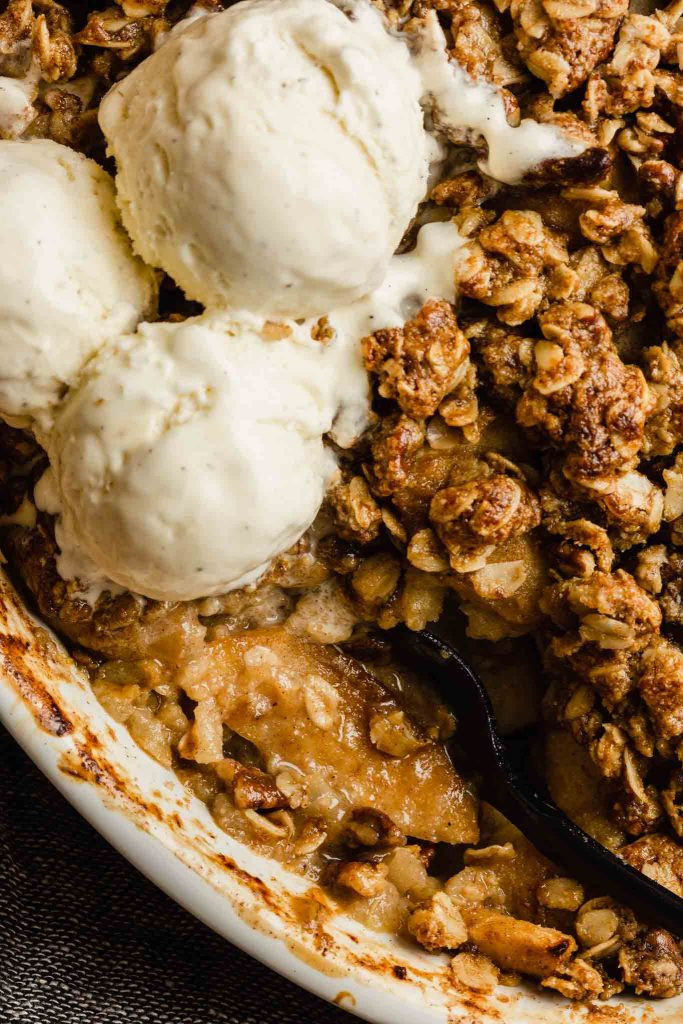 close up of apple crisp with melted ice cream dripping over it