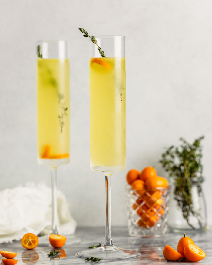 champagne glasses set on a marble table and filled with a yellow drink, kumquats and thyme sprigs