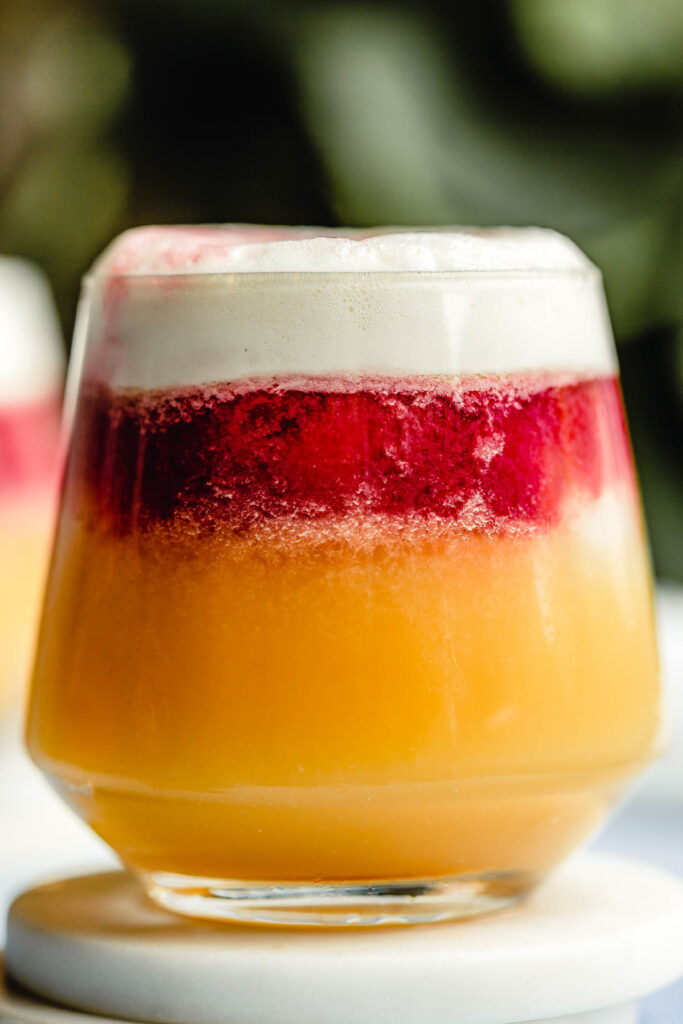 a layered cocktail in a rocks glass. bottom layer is orange-yellow, middle layer is red and top layer is white