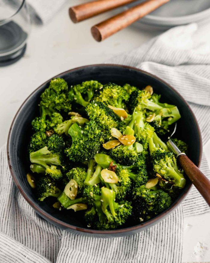 sauteed broccoli in a white bowl with a wooden spoon