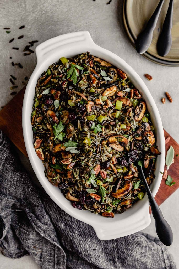 wild rice stuffing in a white oval baking dish set on a wood board on a gray table