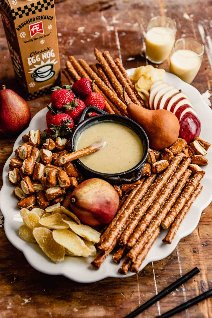 large white platter stacked with pretzels, pears, strawberries, candied ginger with a black pot of fondue in the middle