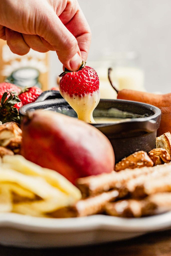strawberry being dipped in white chocolate fondue