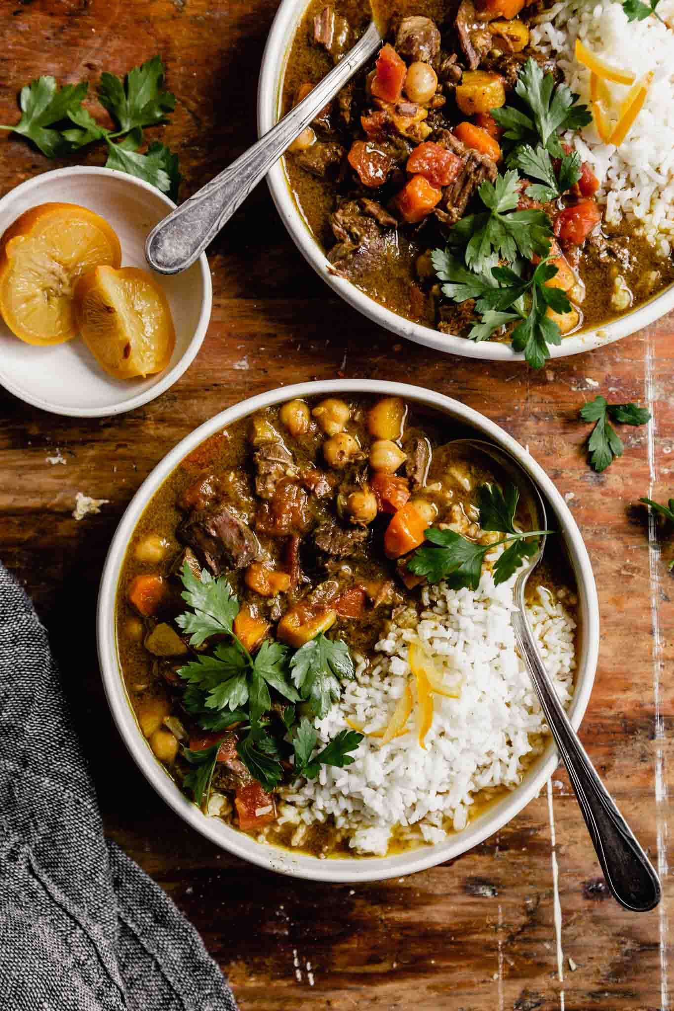 lamb stew with chickpeas, parsley, and rice in a white bowl set on a wooden table