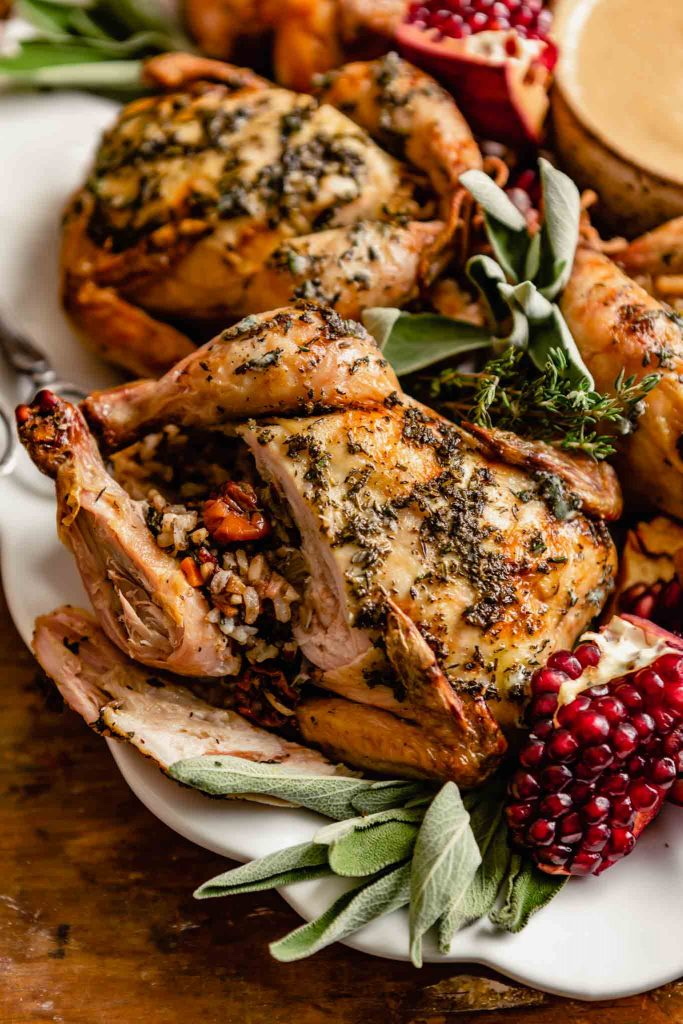 roasted cornish hens on a large white platter with one hen cut open showing the wild rice stuffing