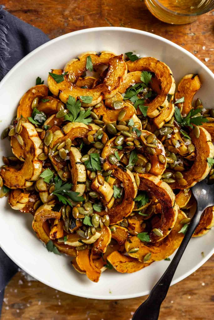 roasted delicata squash slices in a white bowl topped with pepitas, parsley and flaky sea salt.