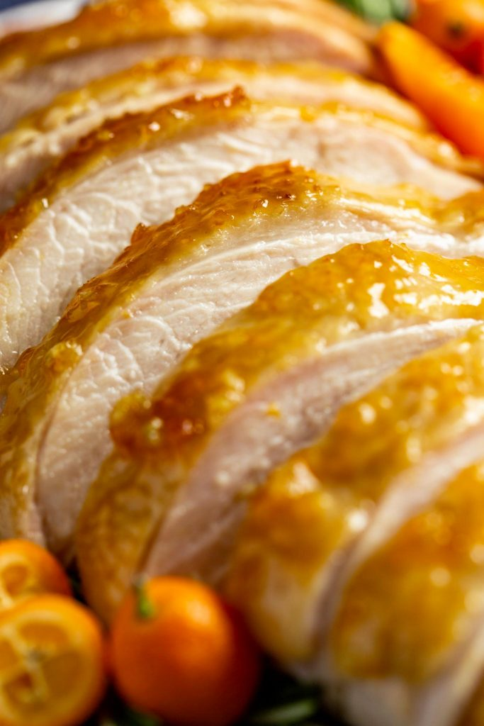 close up of sliced oven-roasted turkey breast with skin on