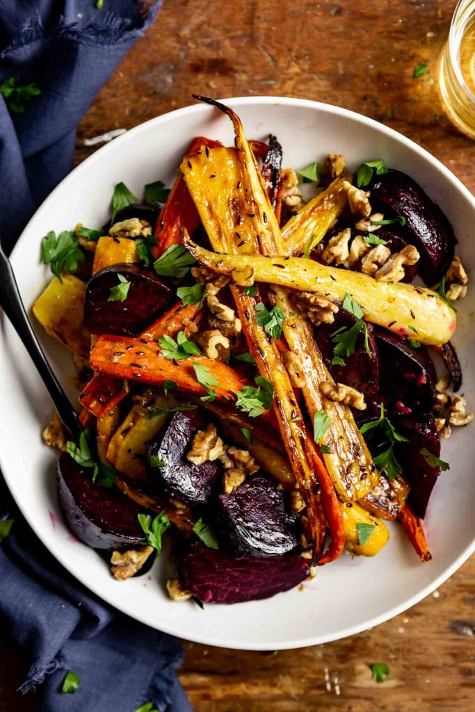 roasted carrots and beets in a white bowl set on a wooden table with a blue napkin and a glass of white wine