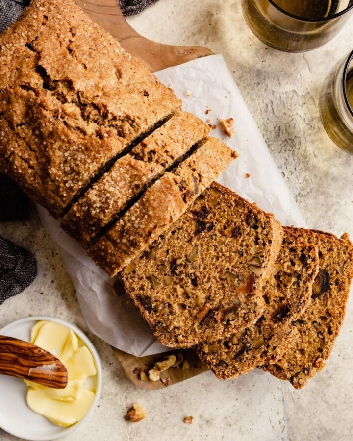 brown bread studded with chopped dried fruit and nuts, set on a parchment-lined wood board set on a table with a butter dish and brown cups set around it