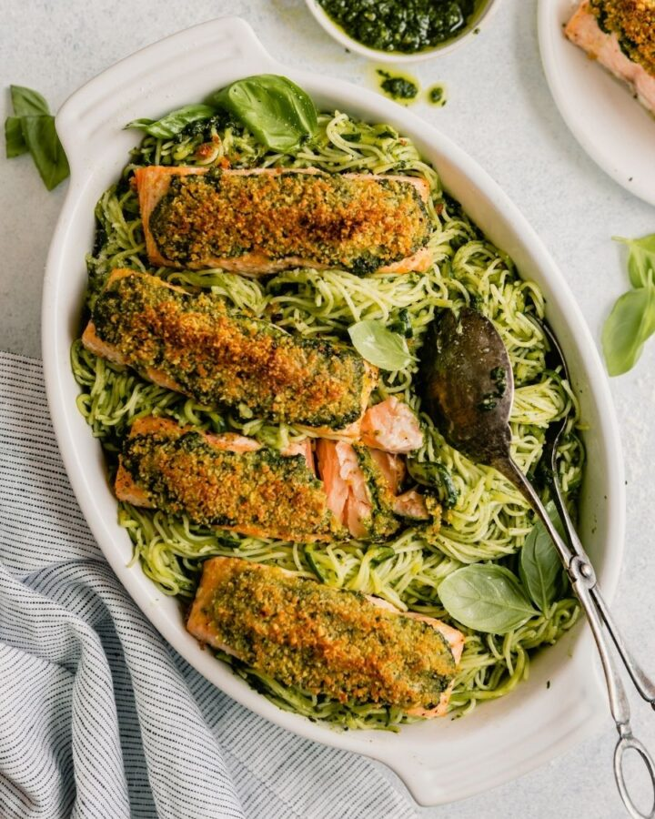 pesto pasta in a white oval serving dish topped with breaded salmon fillets