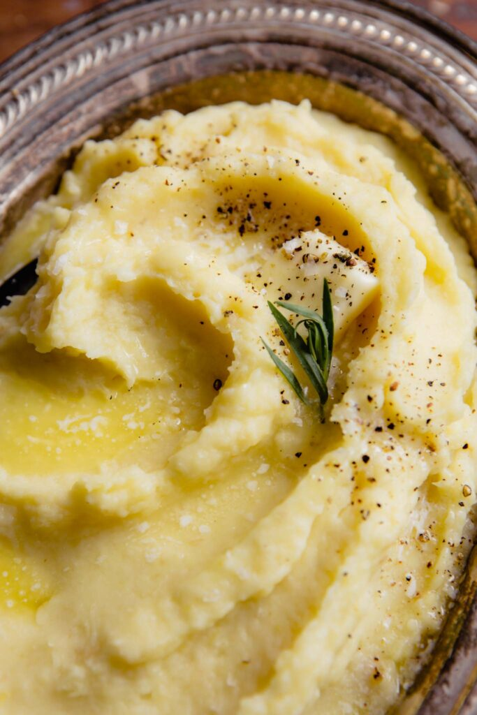 creamy parsnip and potato mash in a silver oval dish with a pad of butter, pepper, salt and tarragon sprinkled over top