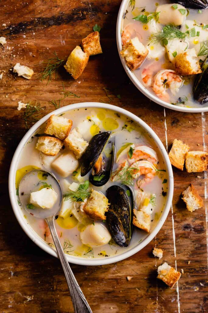 mussels, shrimp, scallops and chunks of white fish in broth with herbs and croutons in a white bowl set on a wood table