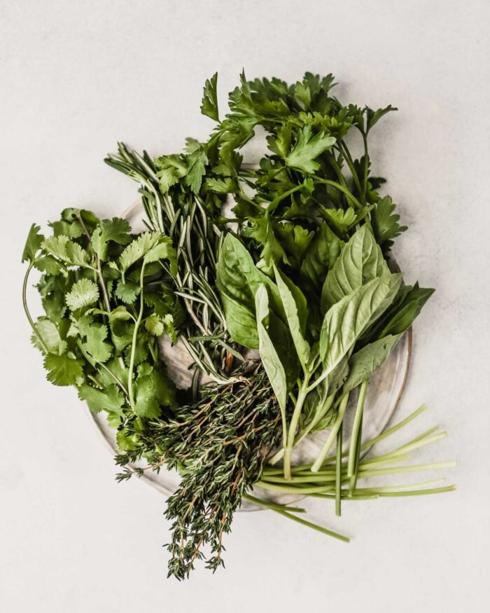 plate filled with a variety of fresh herbs