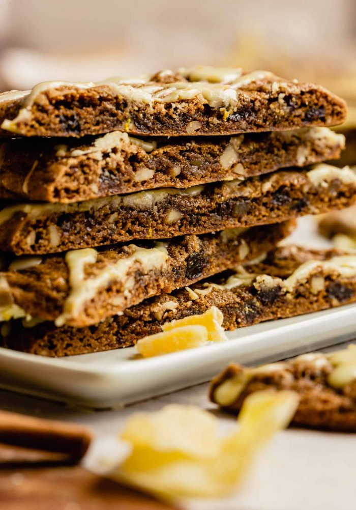 image of stacked spiced molasses cookies on a white plate set on a wood table