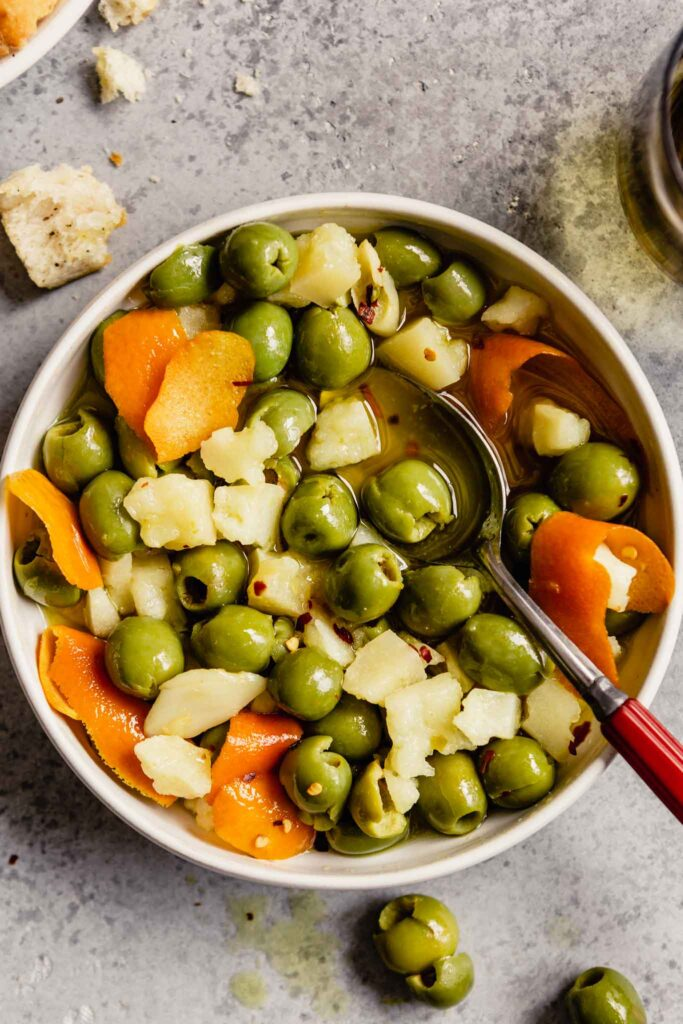 white bowl filled with green olives and chunks of cheese with a red-handled spoon set in the bowl