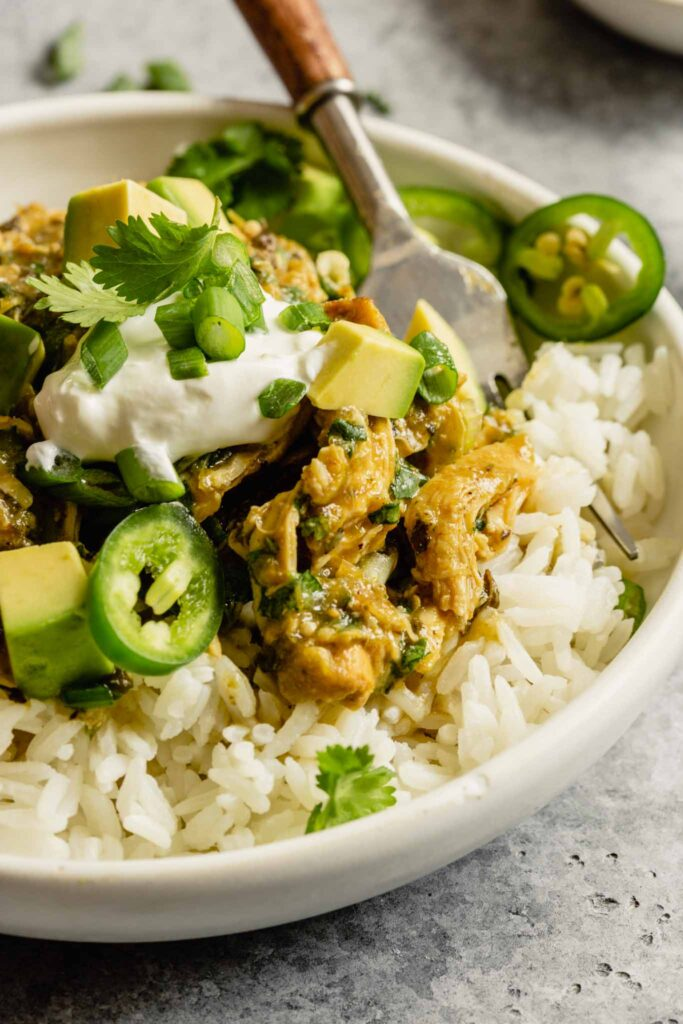 close up of salsa verde chicken on top of white rice in a white bowl topped with avocado, jalapeno slices and cilantro