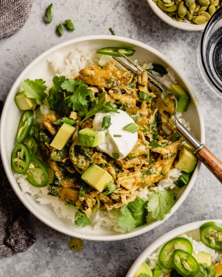 shredded salsa verde chicken in top of white rice in a white bowl garnished with sour cream, avocado, scallions, and cilantro