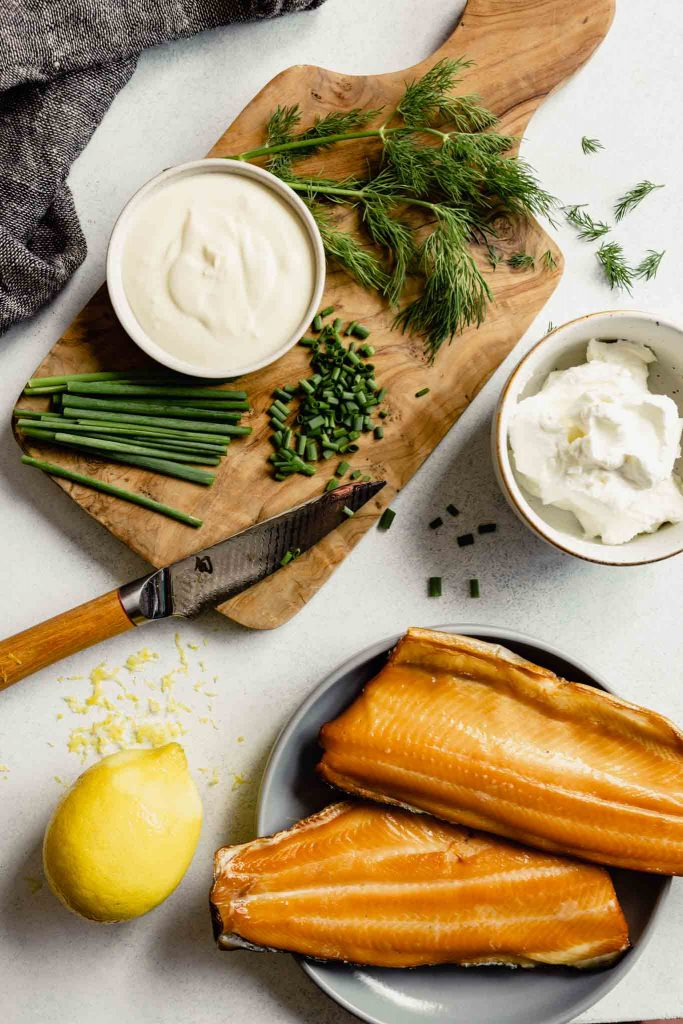 smoked trout, yogurt, creme fraiche, chives, lemon and dill arranges on a cutting board on a table with a napkin